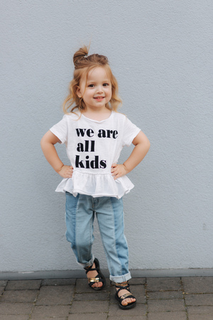 Beautiful little girl dressed in white shirt and jeans stand in front of gray wall. happy children