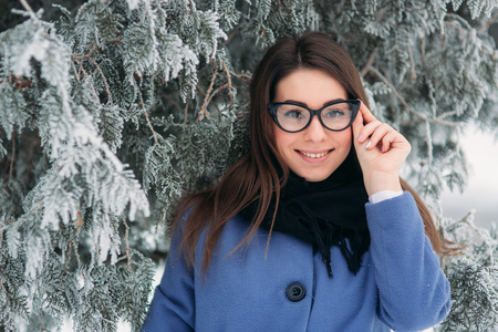 Portrait of happy young woman wearing scarf and blue coat stands next to the Christmas tree. black glasses Foto de archivo