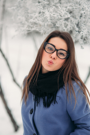Beautiful winter portrait of young woman in the winter snowy scenery. New year