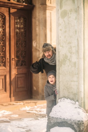 A joyful boy in a coat is playing with father in winter