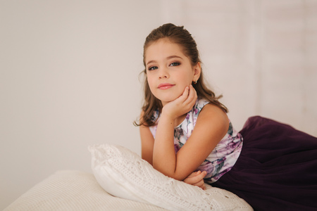 Happy child female in purple dress. Beautiful makeup and hairstyle 免版税图像