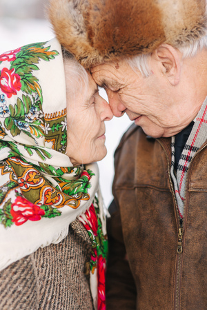 Portrait of happy senior couple. Elderly woman kiss her husband in weighty. old couple walkink in the park in winter time. Happy family. Gold wedding Banque d'images - 116053847