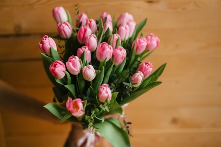 A bouquet of pink tulips in womans hands. Woden background
