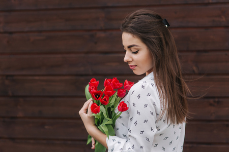 Young girl with bouquet of red tulips stand outside in front of wooden background. Happy female got e bouquet of flowers