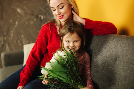 Mom and daughter sitting on sofa with bouquet of flowers. Mothers day