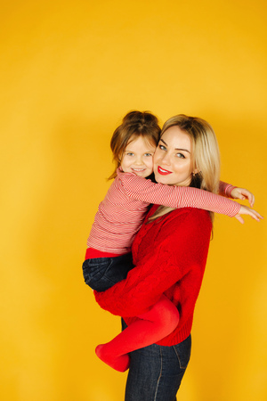 Five year old girl on mothers hand. Little girl with her blond hair mom. Yellow background