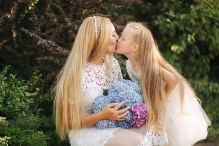Mom with daughter in white dresses spend time in the park. Blond hair female. Mother weaves pigtails daughter outside