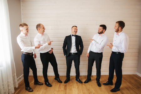 Handsome groom with his groomsman at home. Five man. Groom dressed in suit, gromsmen in white shirt. Funny guys on the wedding