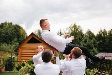 Stylish groomsman with groom standing on the backyard and prepare for the wedding ceremony. Friend spend time together outside