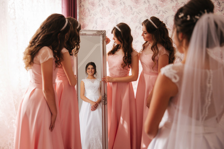 Bridesmaid standing by the mirror and help bride look at yourself. Big mirror at home. Happy girls in same dress