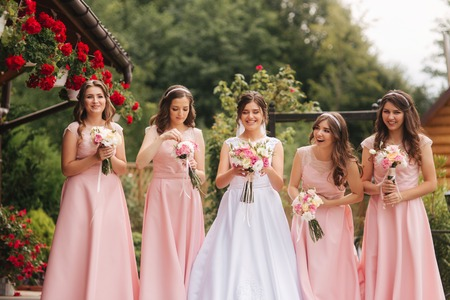 Happy bride with bridesmaid hold bouquets and have fun outside. Beautiful bridesmaid in same dresses stand by the charming bride in long wedding dress Stock Photo