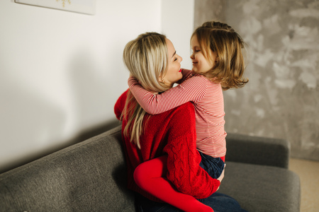 Little girl in red tights with mom in red sweater. Happy family at home. Daughter hug her mother