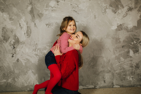 Happy family on the photosession in studio. Mother and daughter