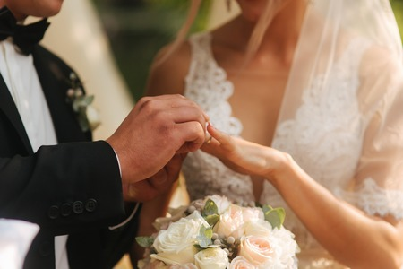 Close up of hands groom and bride wearing a ring