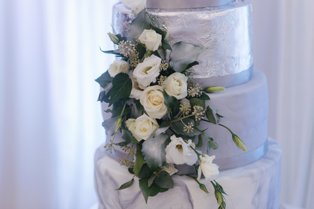 Beautiful wedding cake decorated with flowers. Silver and white color