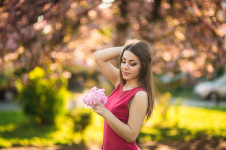 Charming girl in beautiful pink dress hold bunch of sakura in hands. Beautiful european girl near the japanese tree