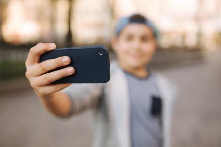 Junge macht ein Selfie auf dem Smartphone im Zentrum der Stadt. Netter Junge im blauen Hut. Stilvoller Schuljunge