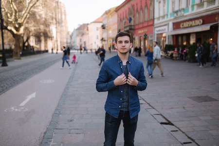 Young stylish man stand in centre of the city. Man use wireless headphones