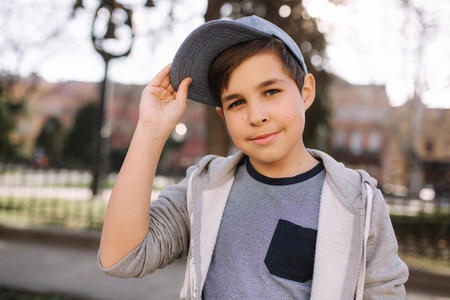 Stylish little school boy in blue cap posing outside for photo. Boy walking in the city in sping summer weather Imagens