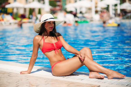 A Sexy lady in a big beach hat sunbathing by the the swimming pool. Beautiful model in pink swimsuit Stock Photo