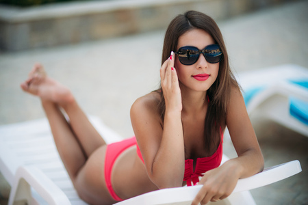 Beautiful lady in sunglasses lies on a sunbed in front of the pool