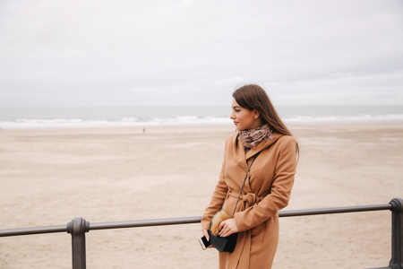 Back view of woman in brown coat standing along North Sea and looking at the waves