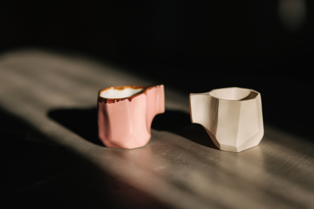 Ceramic cup for coffee on the table. Right is unfinished, left is ready