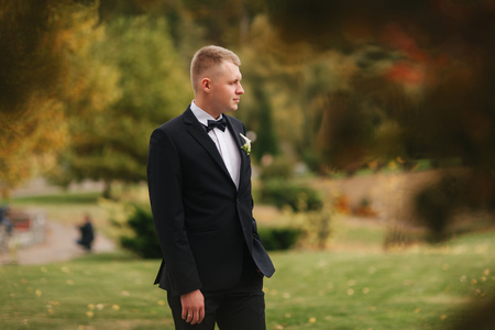 Handsome man in black suit standing outside in autumn. Groom waiting for bride