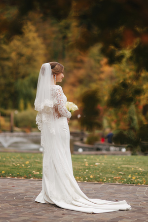 Beautiful bride in elegant wedding dress stant in the park and hold a bouquet of flowers. Charming lady 스톡 콘텐츠