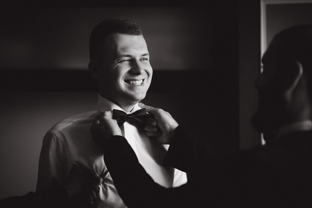 Happy groom stand by the window at home. Morning of groom. Handsome man in suit