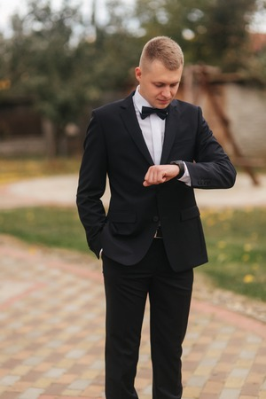 Handsome man in suit look at the watch outside, autumn. Man in black suit with beautiful tie bow