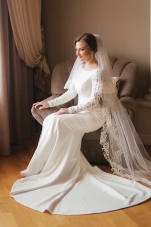 Gorgeous bride sitting on the chair at the home. Beautiful woman in wedding dress Reklamní fotografie