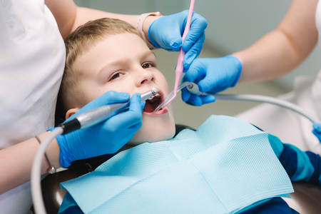 Young boy sitting on the dental chair at the office. Childrens dentist examination baby teeth