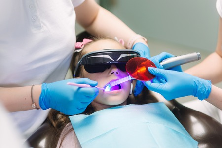 Close up of Little girl in VR glasses and wireless headphones sitting in dental chair