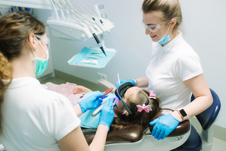 Little girl in VR glasses and wireless headphones sitting in dental chair. Dentist with assistant Stock Photo