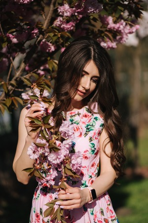 Close up of beautiful woman near the pink tree with makeup close her eyes