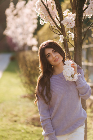 Beautiful girl stand by white blooming three