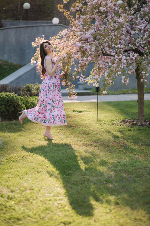 Elegant woman in beautiful dress stand by the pink tree in the park
