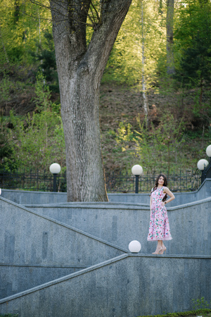 Elegant woman in beautiful dress stand by the stairs in the park