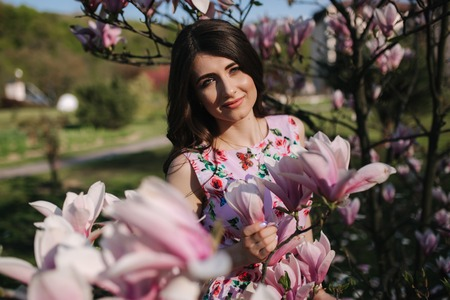 Charming girl stand by the beautiful pink magnolia tree outside. Gorgeous lady Stock Photo