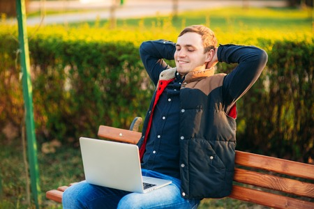 Young businessman finish work on his laptop in the park. Work in internet. Online business