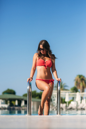 Attractive young woman in pink bikini getting out of a swimming pool. Beautiful long hair tanned female Standard-Bild - 122682929
