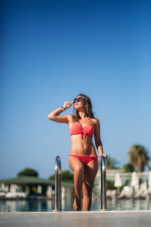 Attractive young woman in pink bikini getting out of a swimming pool. Beautiful long hair tanned female Imagens