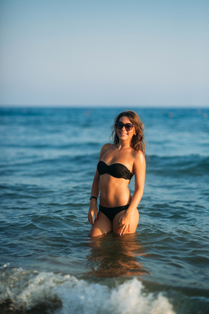 Beautiful lady is waist-deep in the sea. Sexy woman in black bikini wait for waves in the sea Standard-Bild