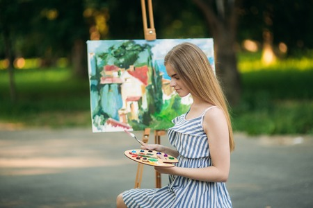 Beautiful blond hair girl sitting on stool and draws a picture in the park using a palette with paints and a spatula