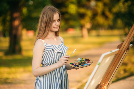 Portrait of Blond hair girl in dress drawing a picture in the park