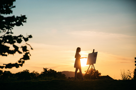 Silhouette of a blonde girl paints a painting on the canvas with the help of paints. A wooden easel keeps the picture. Summer is a sunny day, sunset