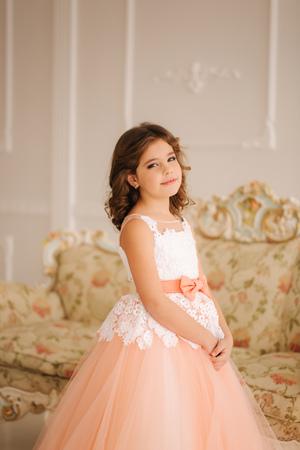 Happy little princess in beautiful dress walk though the big studio
