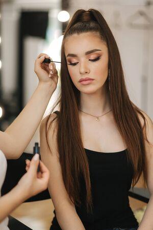 Make-up-Künstlerin, die eine junge rothaarige Frau mit Sommersprossen professionell macht