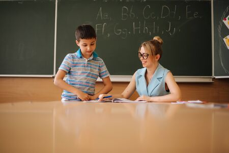 Pretty teacher in classroom sitting at the desk and asking children. education, elementary school, learning and people concept